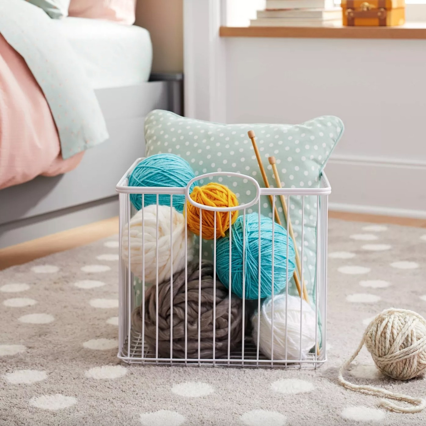 The stackable storage wire bin in white holding yarn, a pillow, and knitting needles