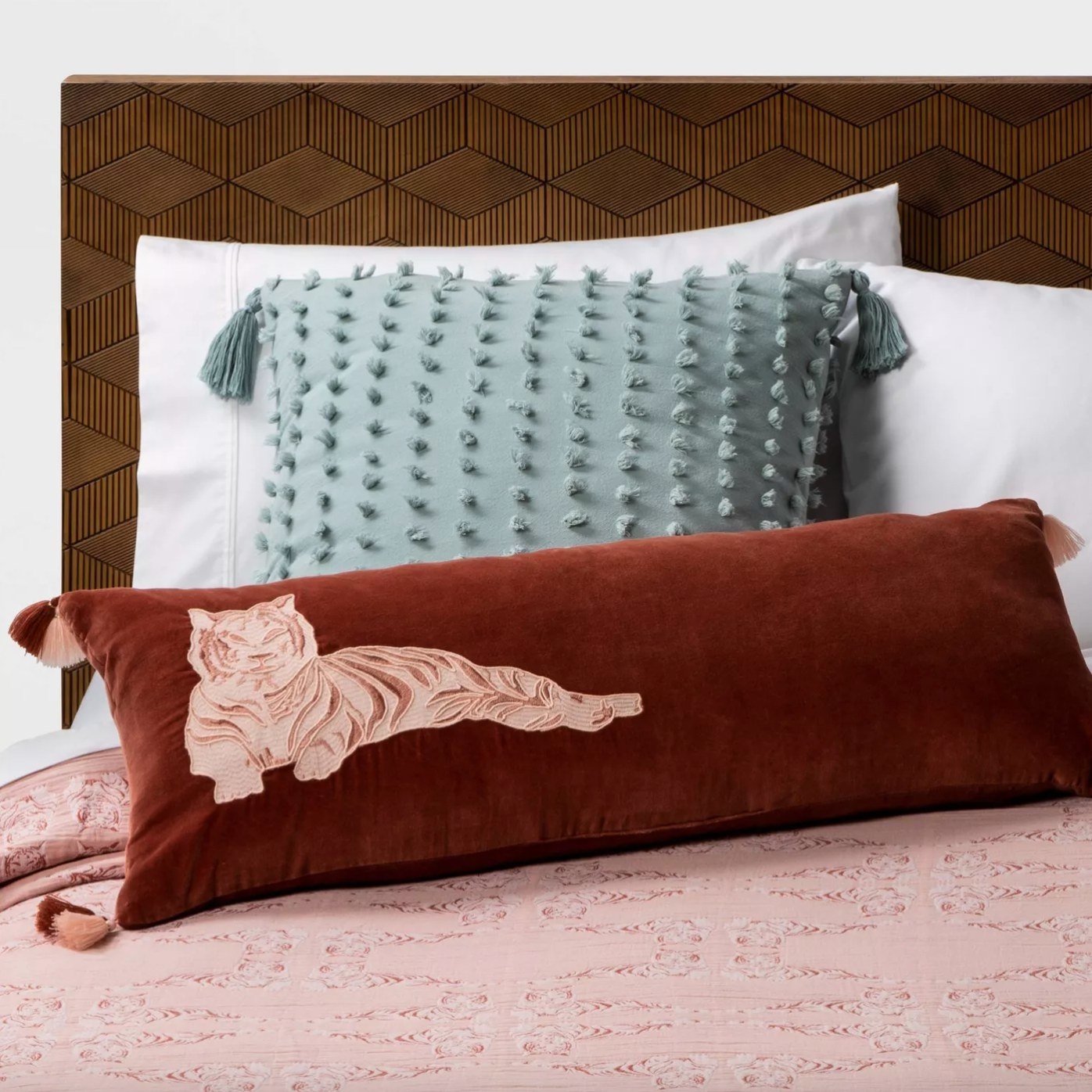 The decorative throw pillow in dusty jade on a bed with a wood headboard
