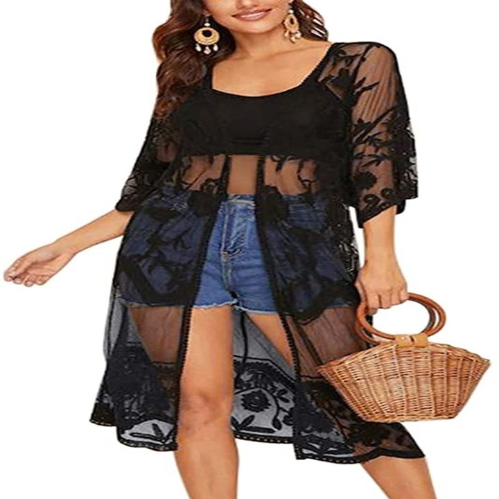 model wearing the knee-length open front lace kimono over a crop top and shorts