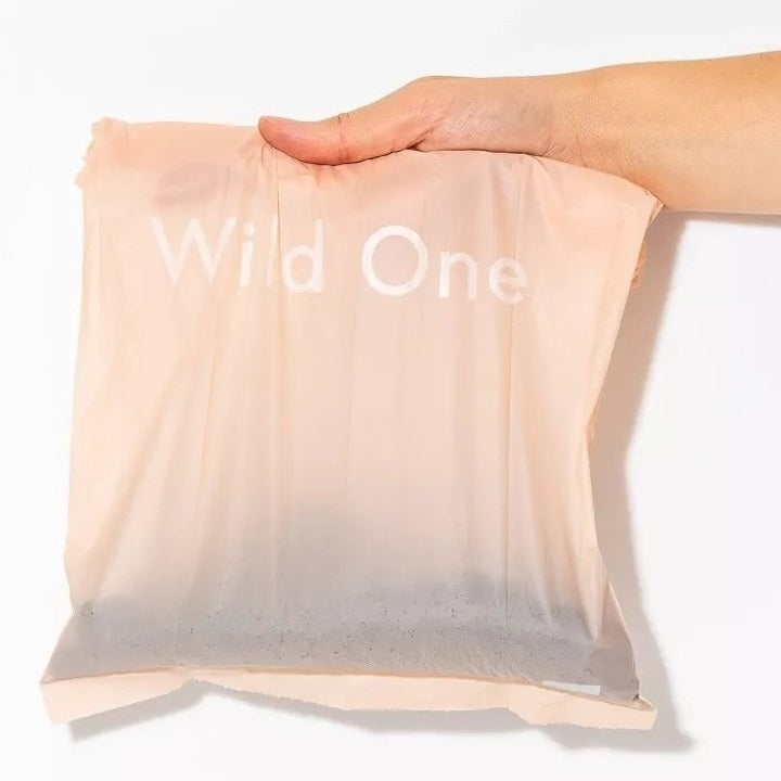 """a hand holding a light pink bag that says """"wild One"""""""