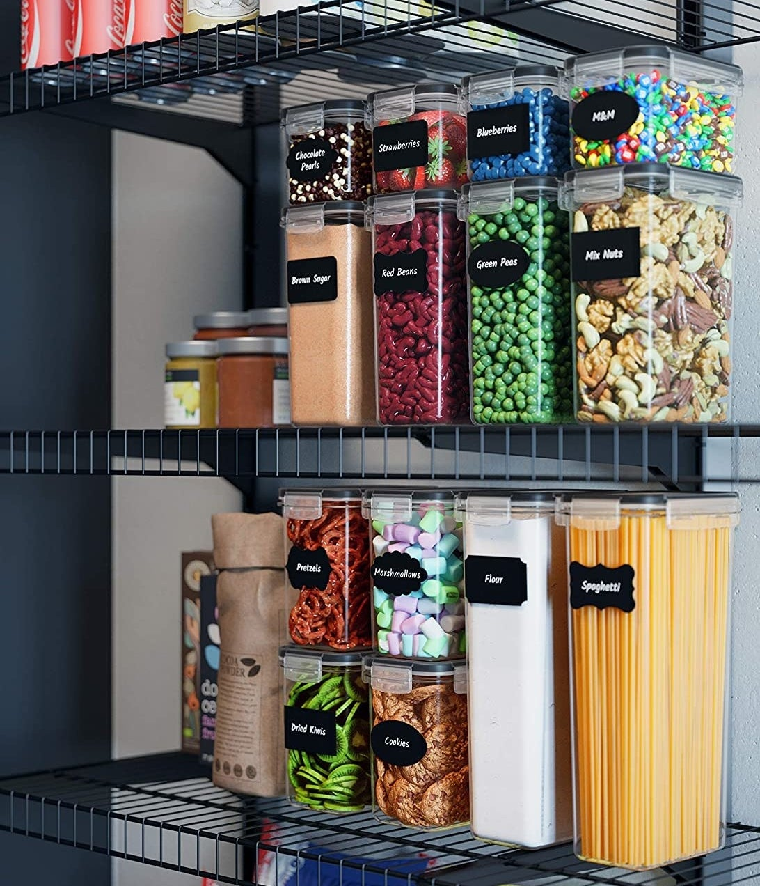 A set of plastic food containers with chalkboard labels arranged neatly on a pantry shelf