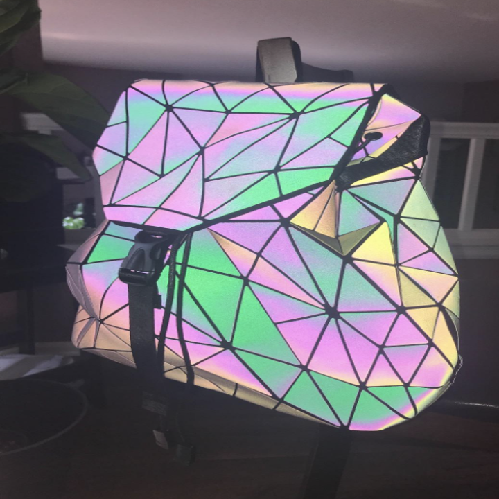 the backpack looking luminous in pastel colors when it's in the dark and light is reflected on it