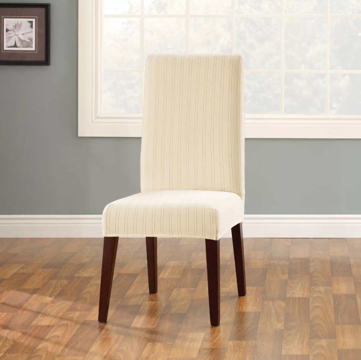 The short dining room chair cover in cream on a chair with wood legs