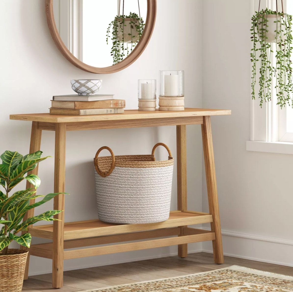 The wood console table holding a basket, books, and candles