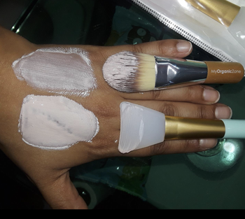 different reviewer comparing regular brush with silicone brush. the silicone brush shows much more mask applied to skin.