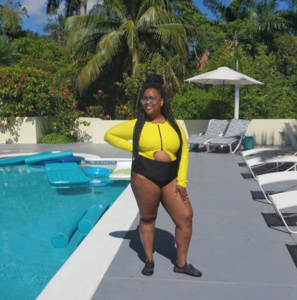 A reviewer in the yellow and black long sleeve swimsuit with a semi-circle cutout at the waist