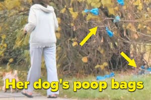 A woman throws a blue bag of dog poop into a tree with dozens of other blue bags