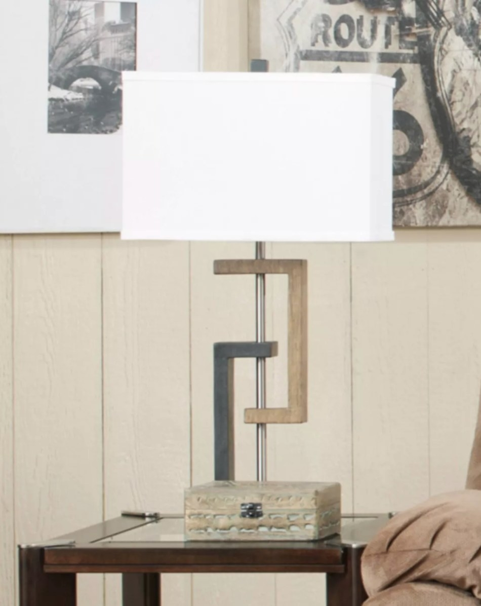 One of the set of two geometric base side table lamps  on a wood end table