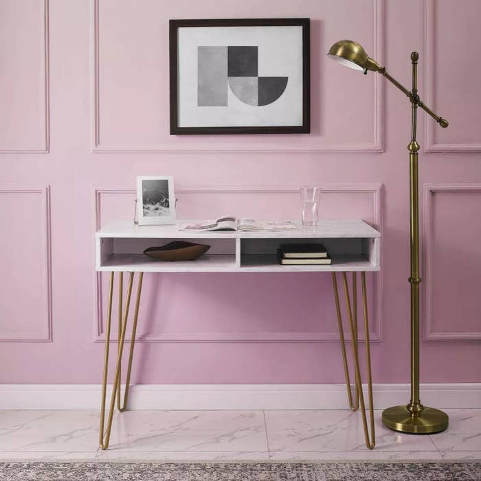 The desk against a pink wall with a magazine on top