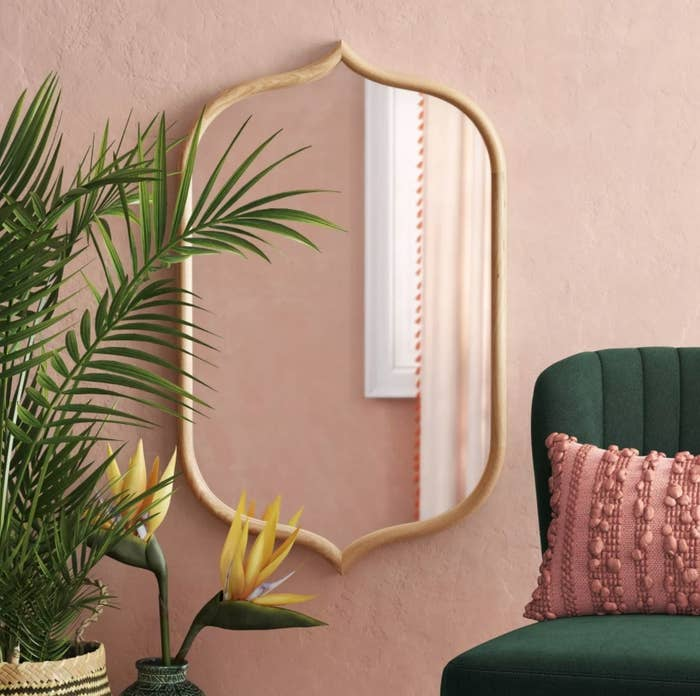 The mirror against a salmon colored wall framed by a large plant and green chair