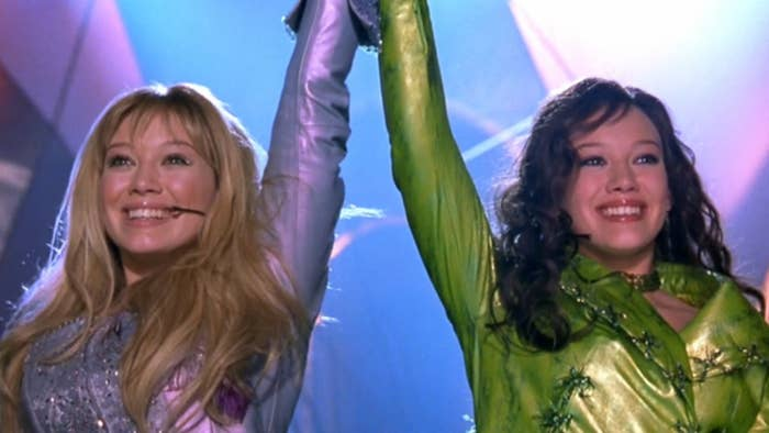 Lizzie and Isabella hold hands and raise there arms up, grinning