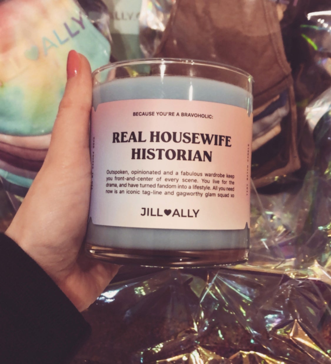 "buzzfeed editor holding a light blue candle with a label that says ""real housewives historian"""