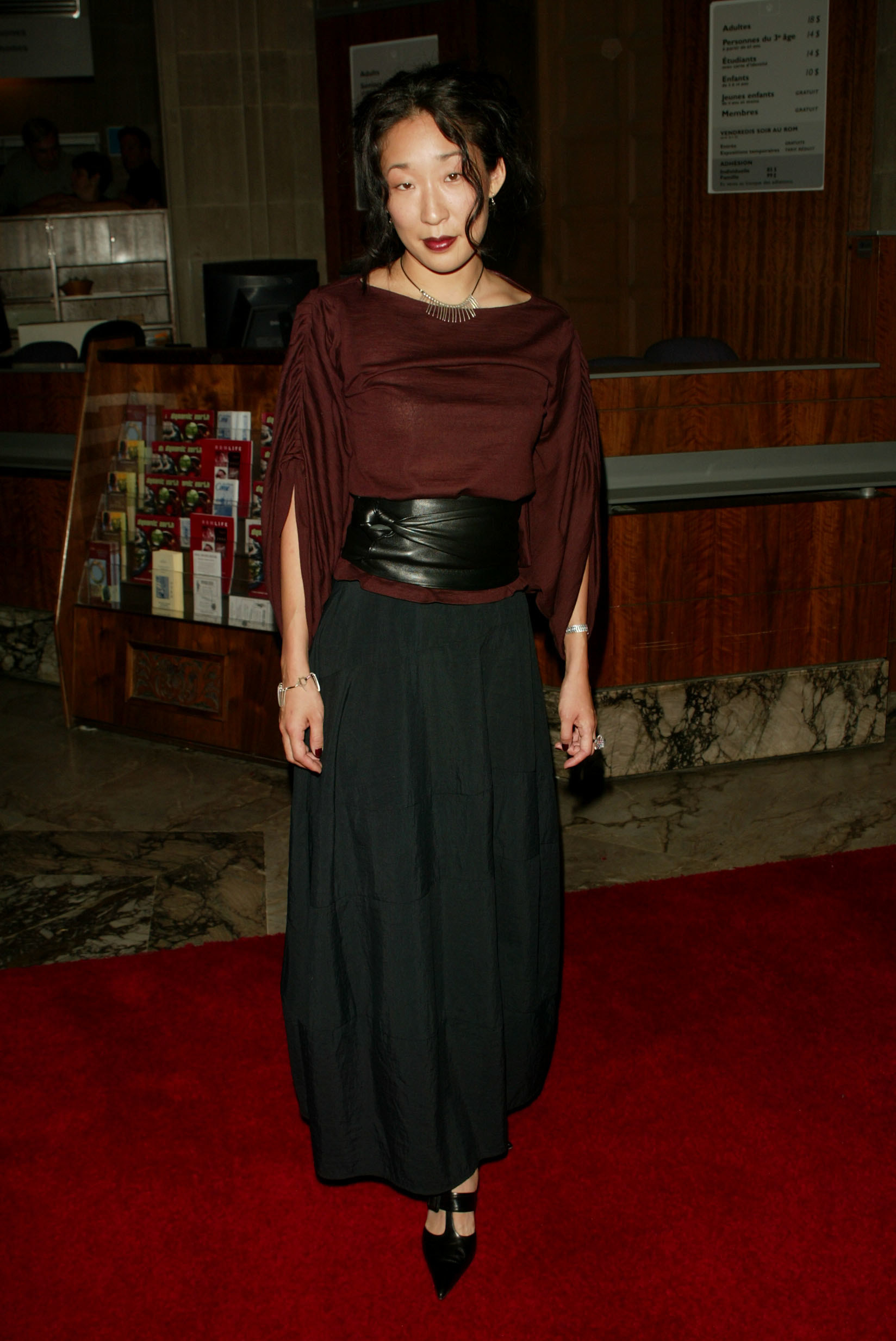 Sandra Oh on a red carpet with a long skirt and black leather belt