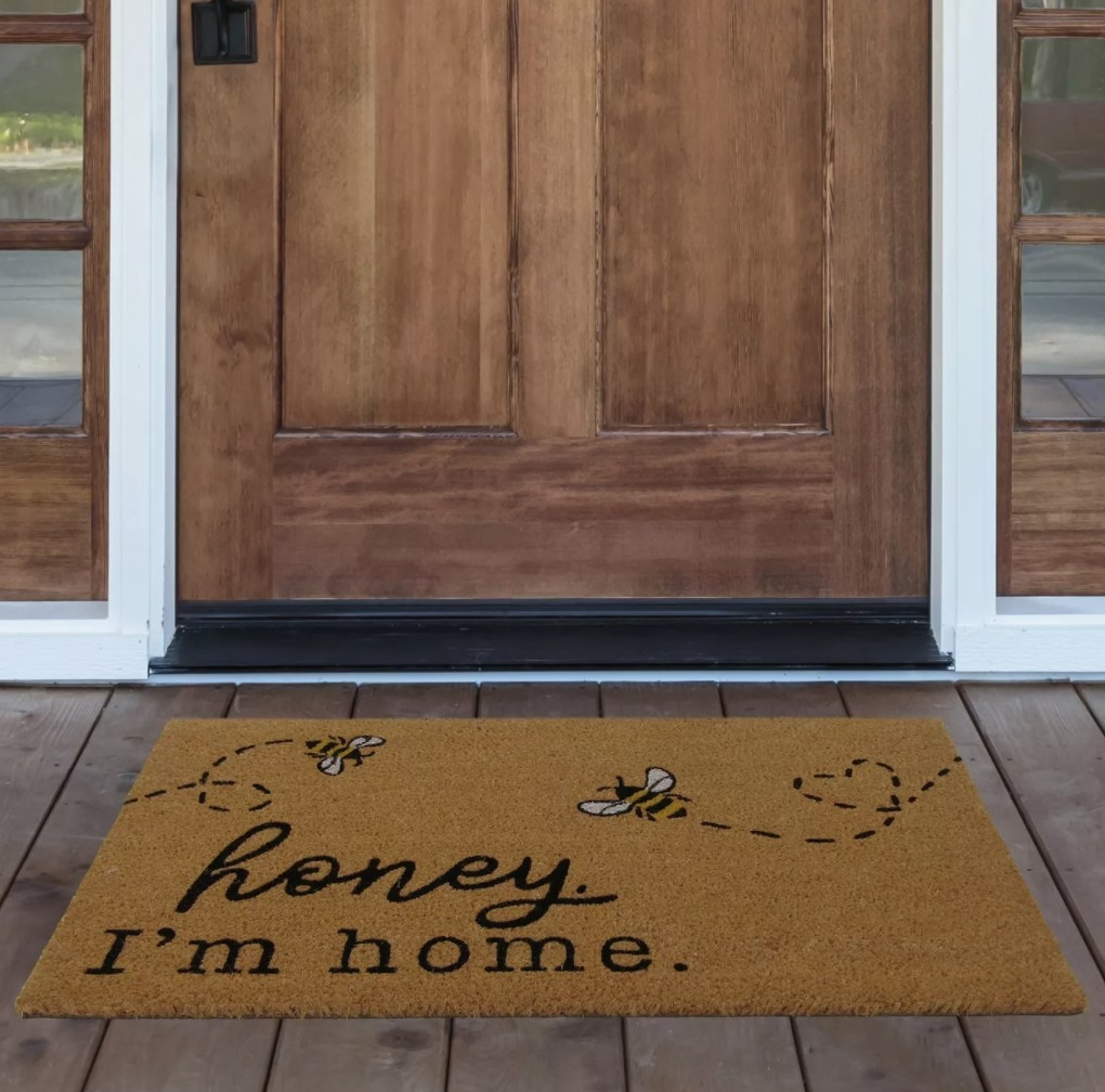 "The welcome mat in front of a door on a porch reading, ""honey, I'm home"""