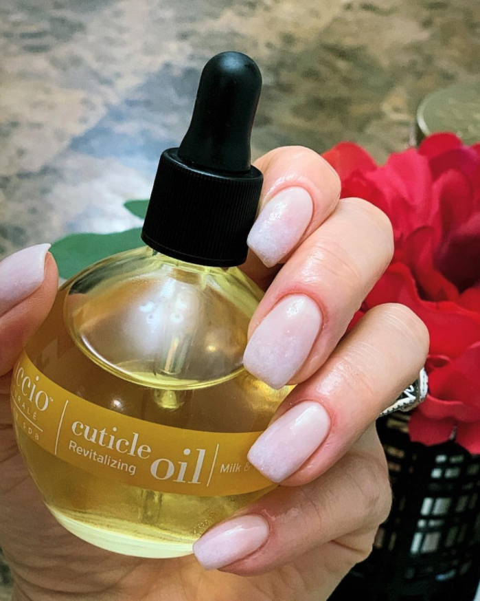reviewer holding jar of oil with healthy looking nails and cuticles