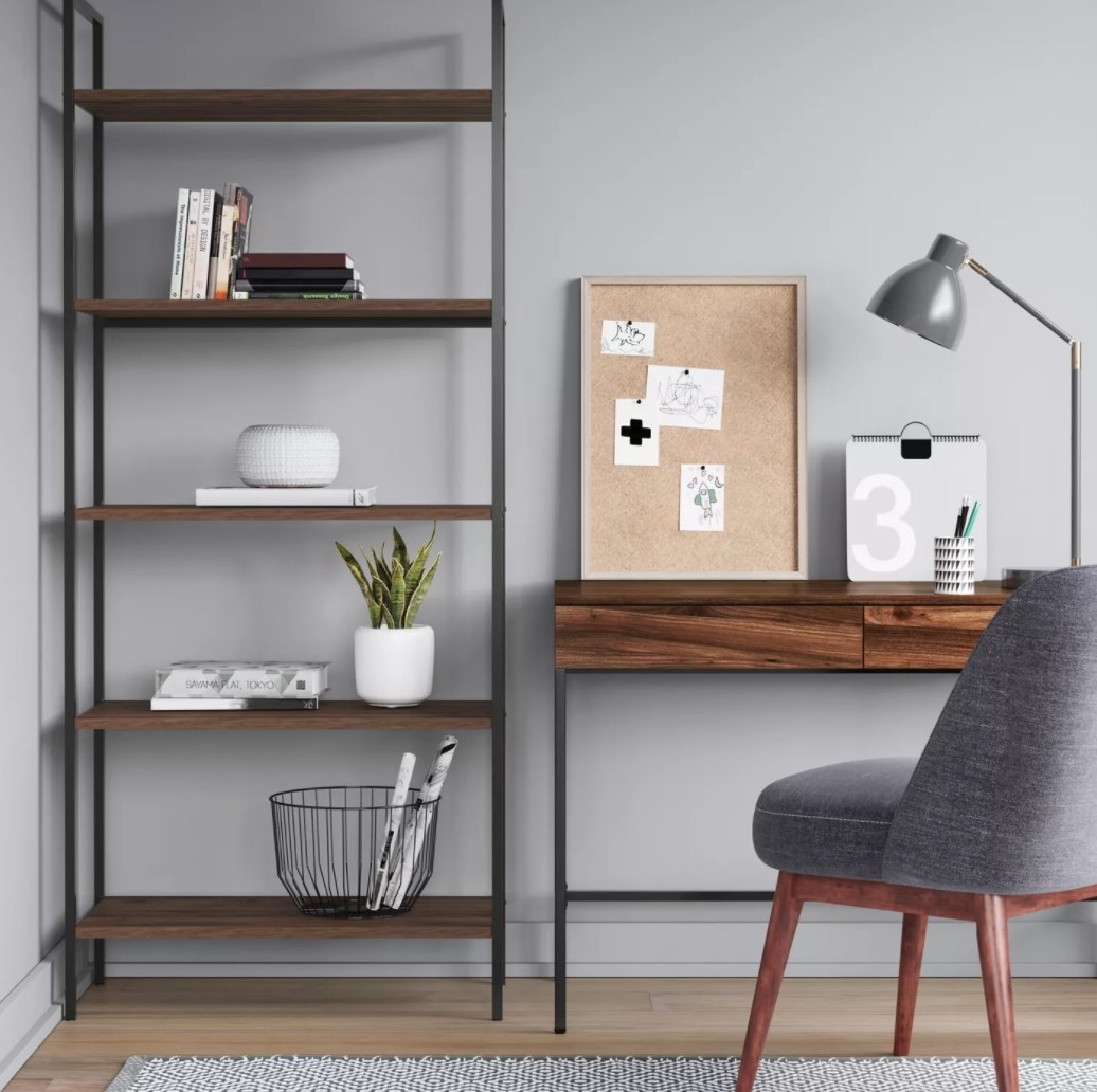 The ladder bookshelf in an office with books and plants set on top