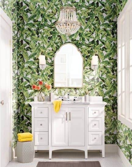 green palm leaf wallpaper on a bathroom wall behind a mirror and white sink