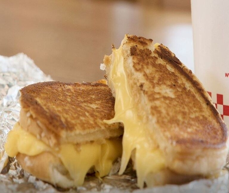 A Five Guys grilled cheese cut into halves.