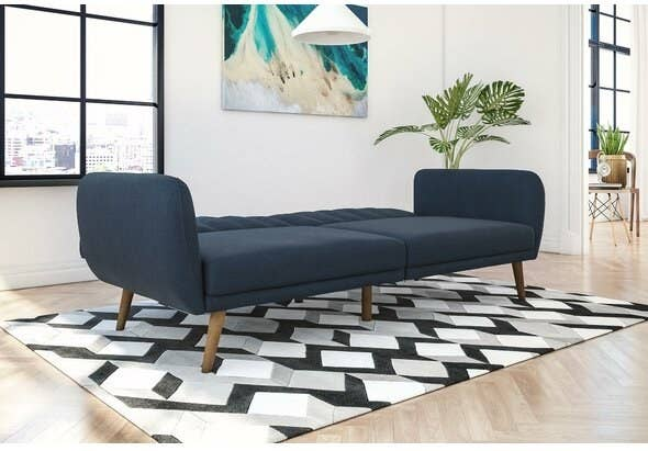 Navy blue sofa converted into a bed sitting in a living room on a black and white rug