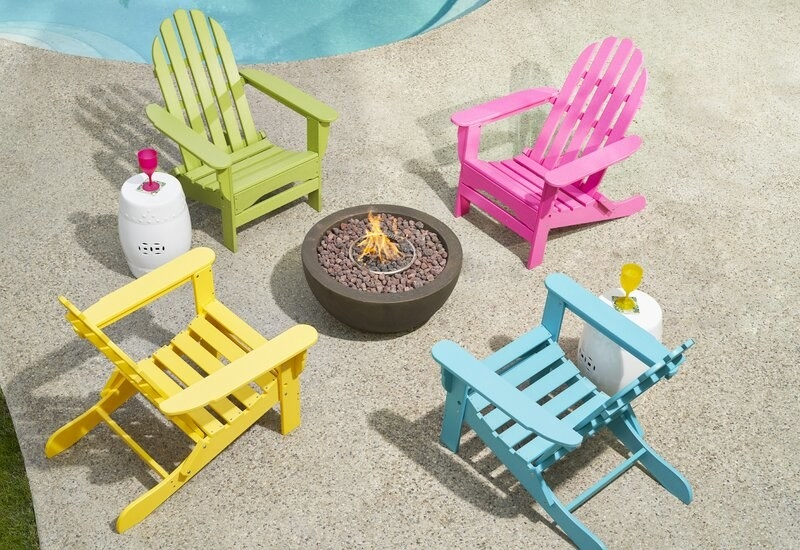 four brightly colored adirondack chairs around a fire pit