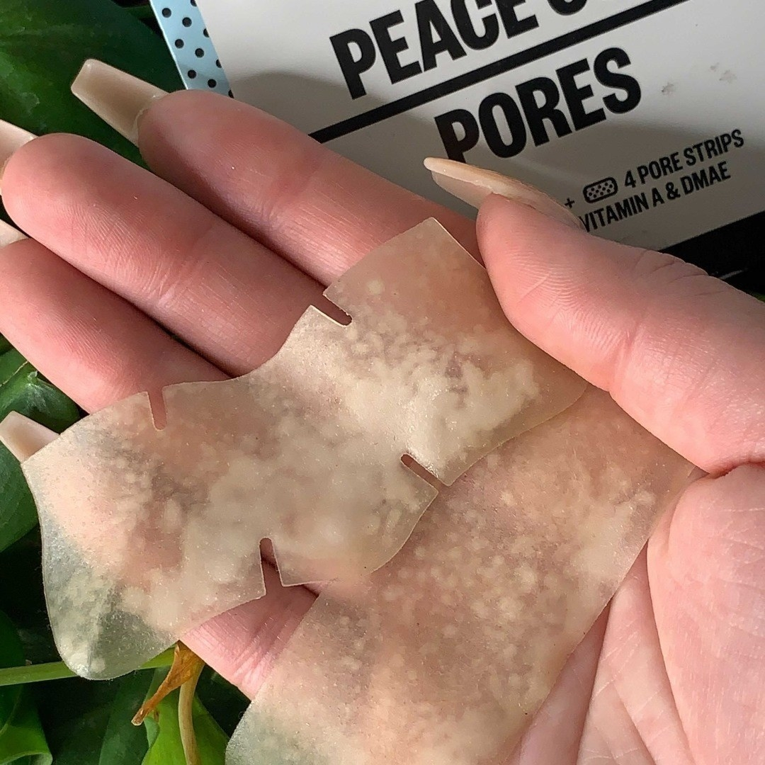 A person holding two pore strips