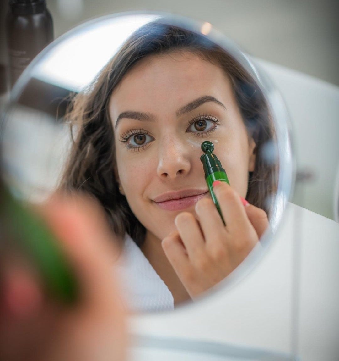 A person applying the cream under their eyes