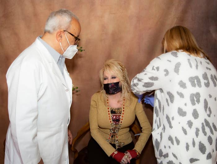 Dolly receives an injection from a nurse while wearing a mask