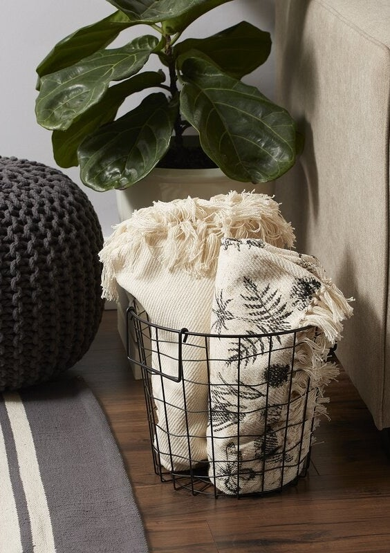 Metal basket with throw blankets inside