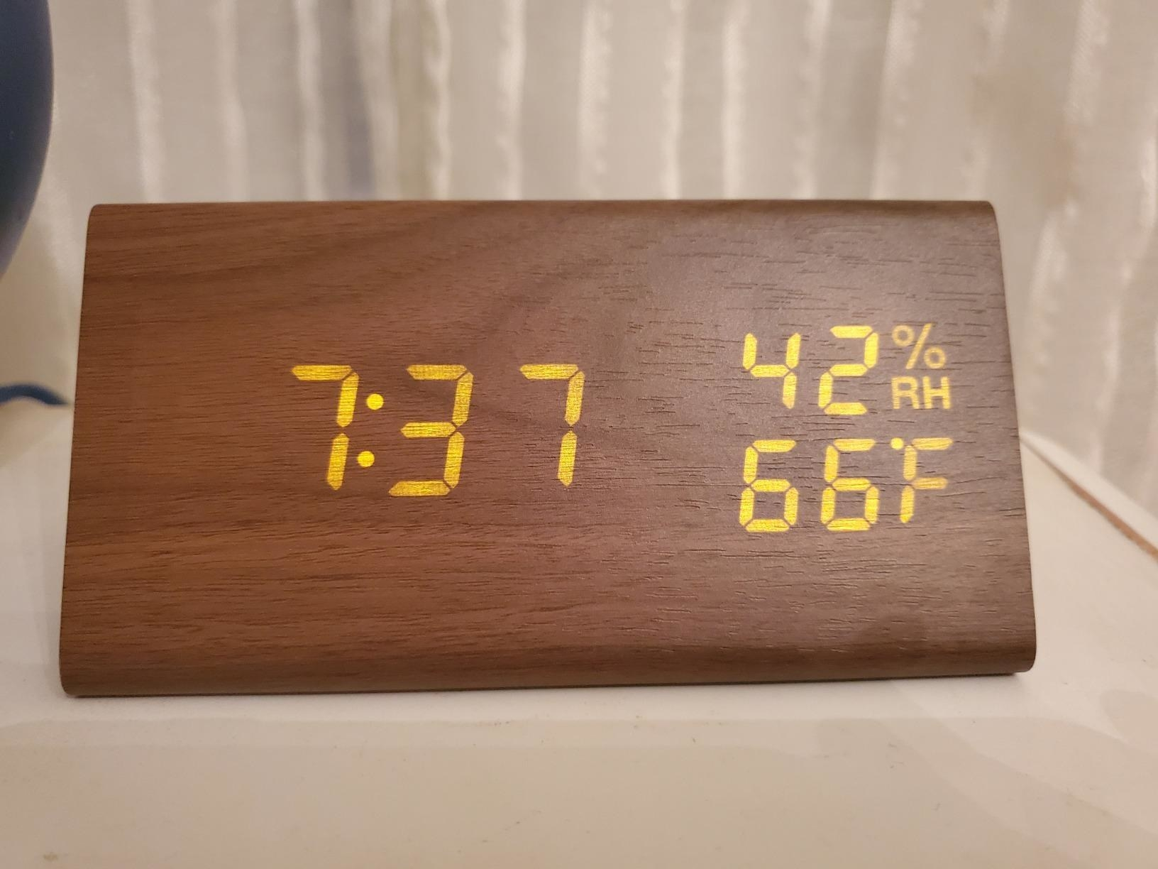 Reviewer image showing plug-in clock with time, humidity, and temperature display