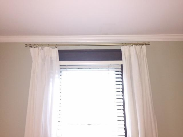 Reviewer showing sturdy gold curtain rod mounted above window