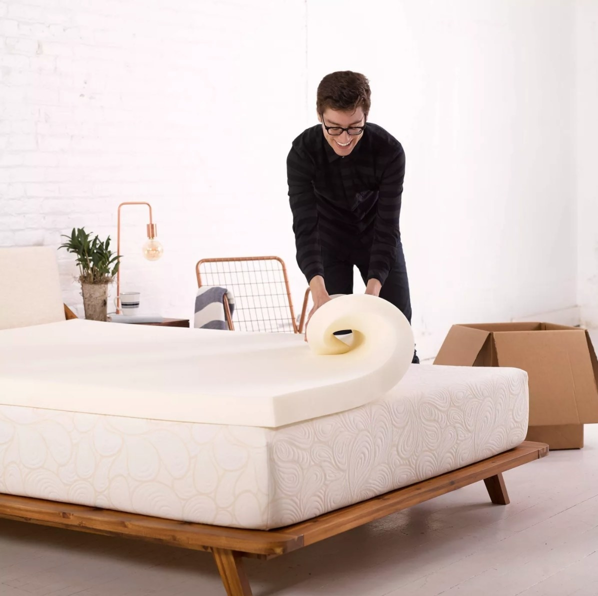 model putting the topper on a mattress