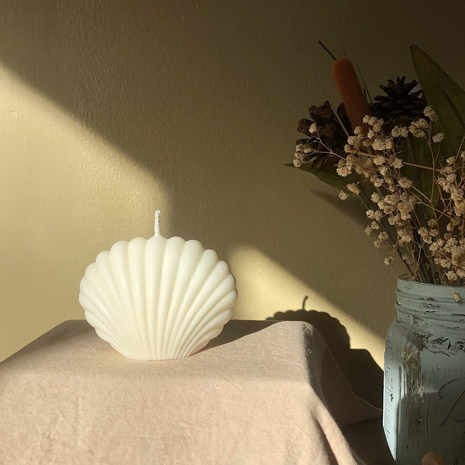 white seashell candle styled next to some flowers in a vase
