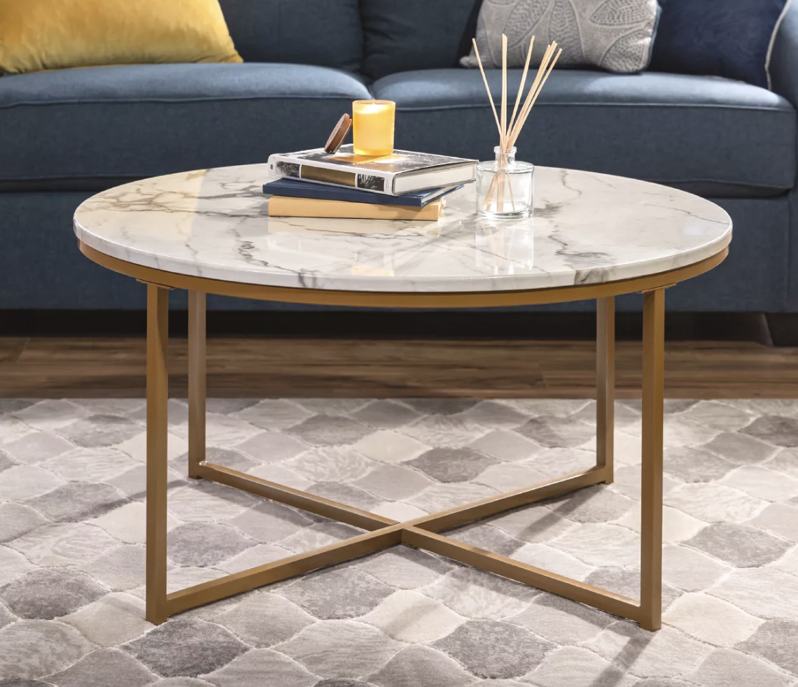 The round marble coffee table with a gold metal frame holding a gold bowl