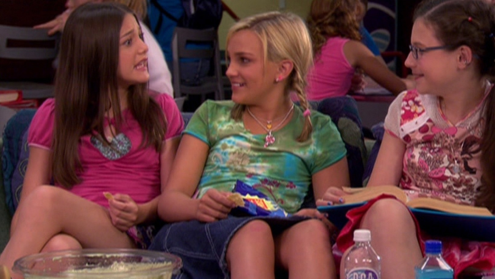 Nicole, Zoey, and Quinn sitting on a couch with books and magazines in their laps