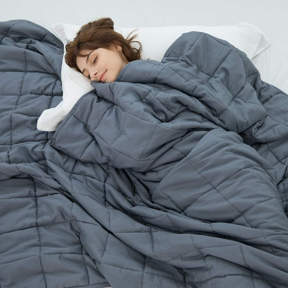 A person sleeping under a weighted blanket