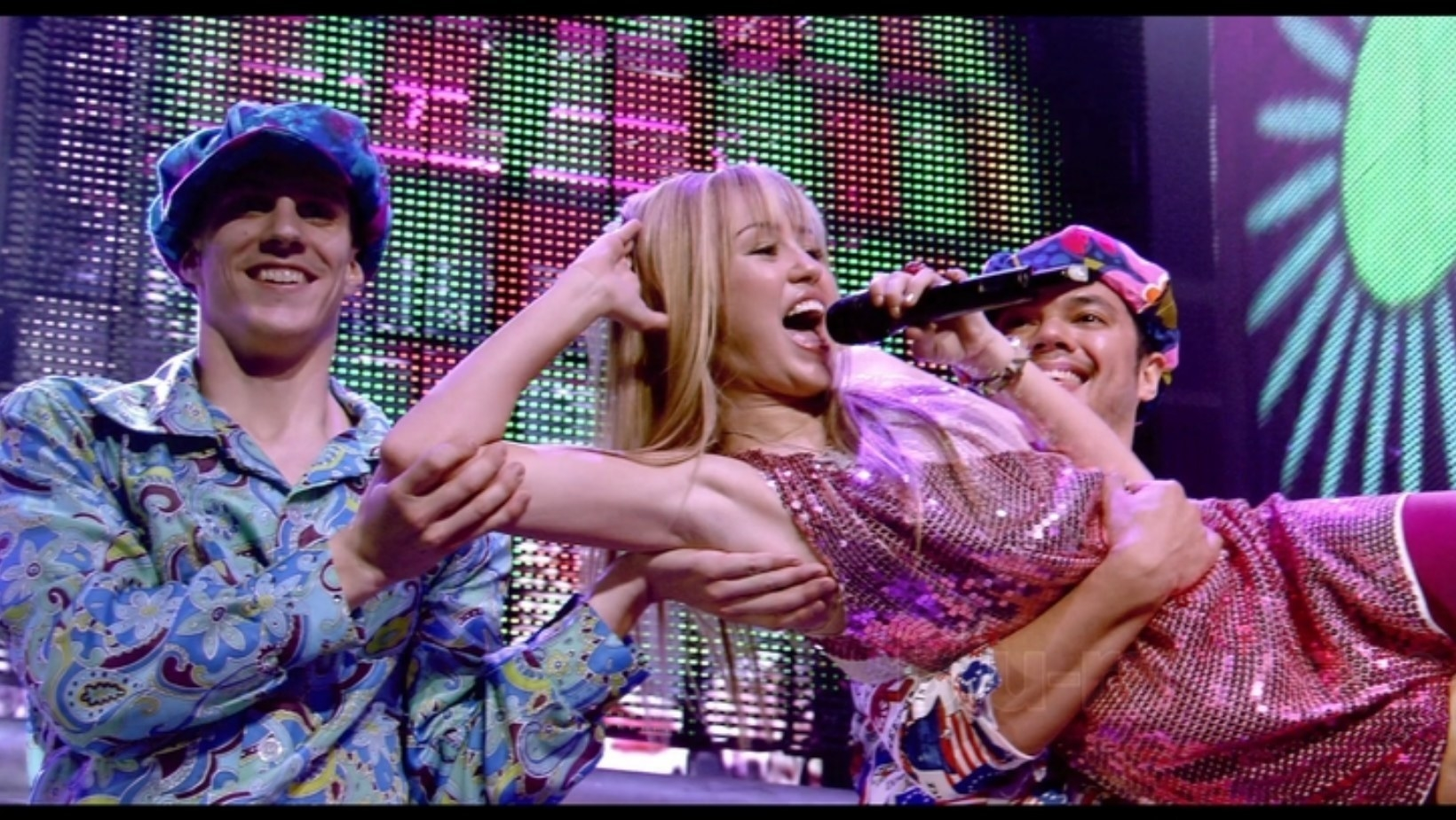 Hannah Montana lies on her side and sings while two people hold her up in the air