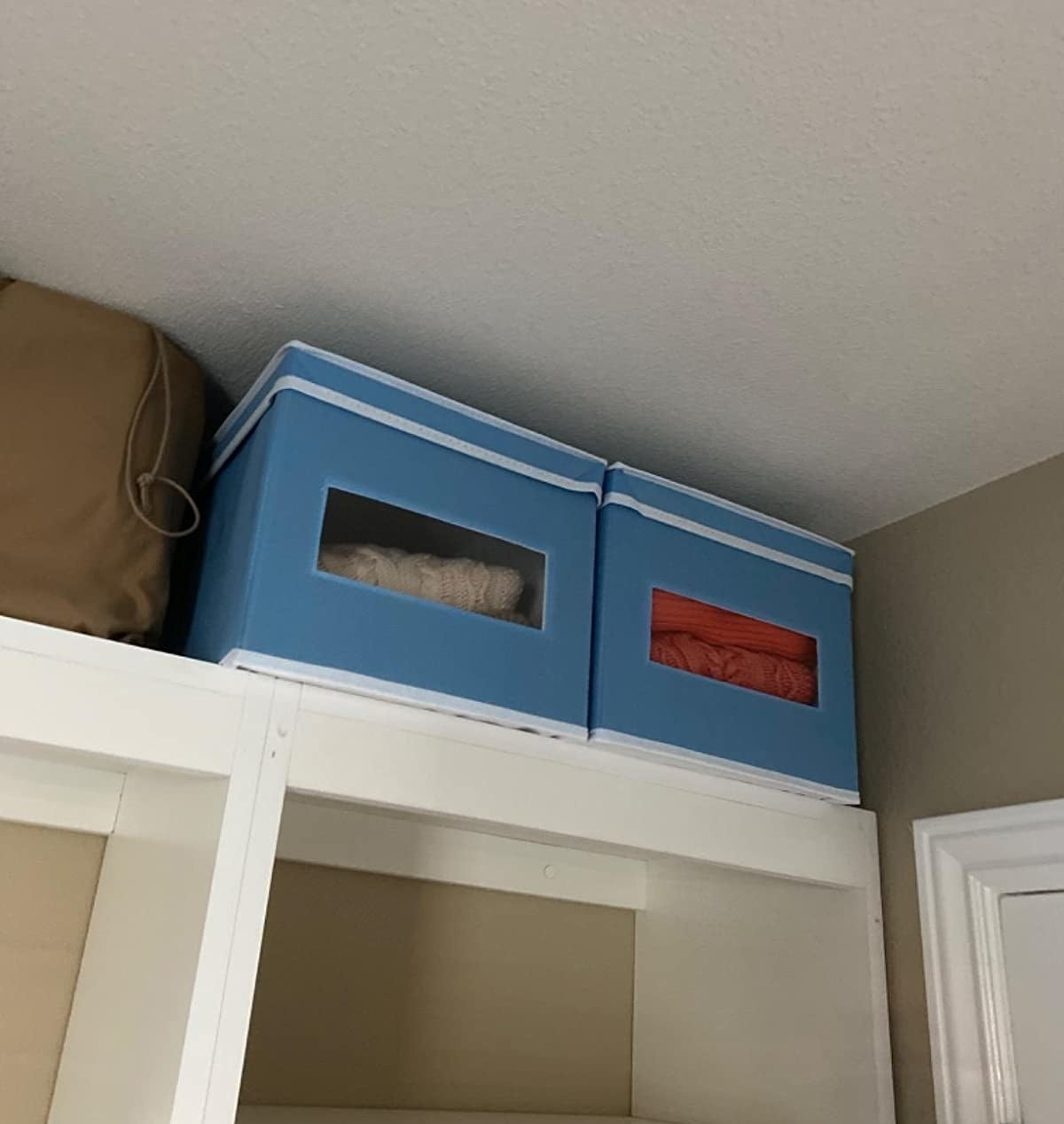reviewer image of two light blue mDesign fabric storage boxes on top of a closet
