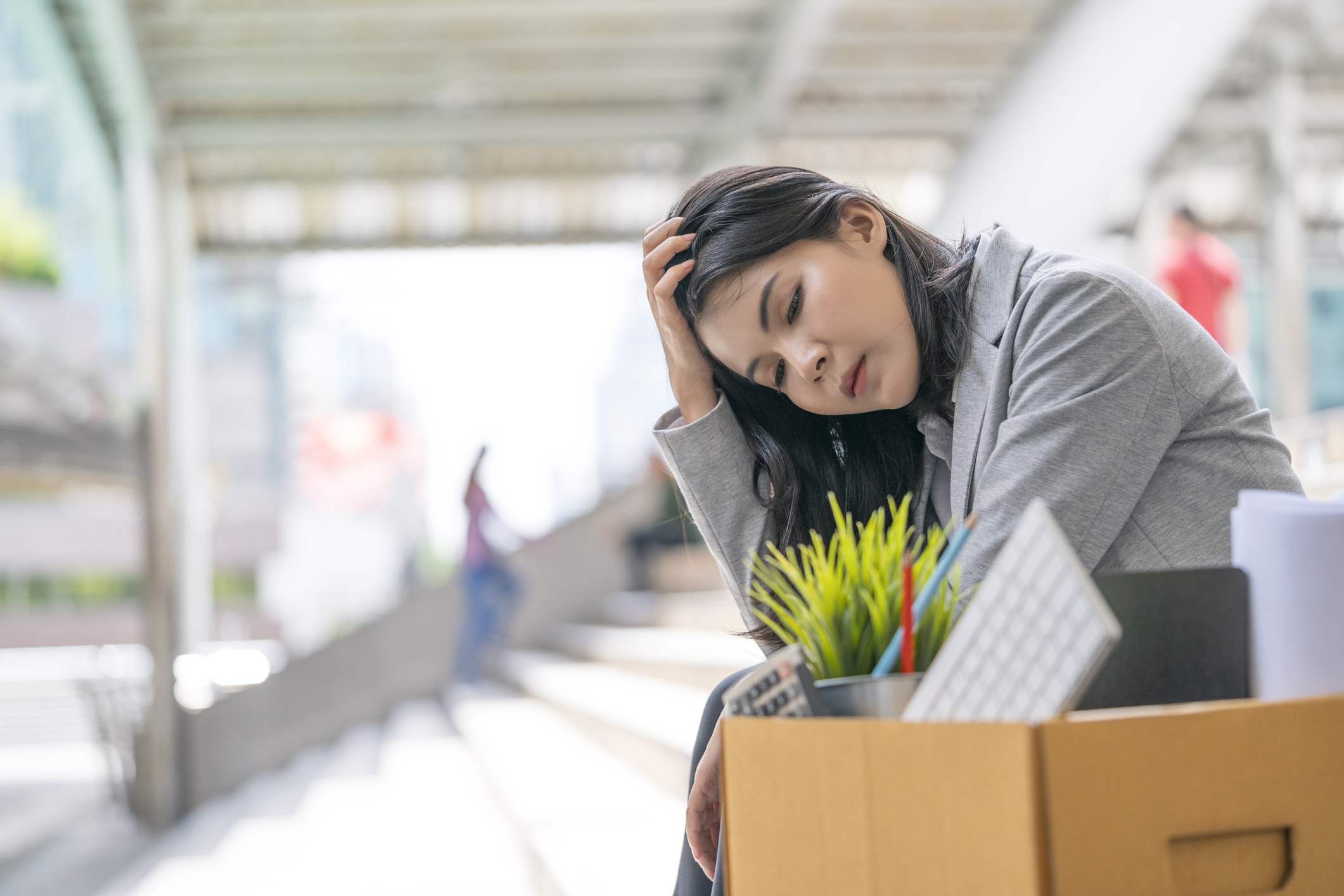 An employee sitting with a box of office supplies, as if leaving a job