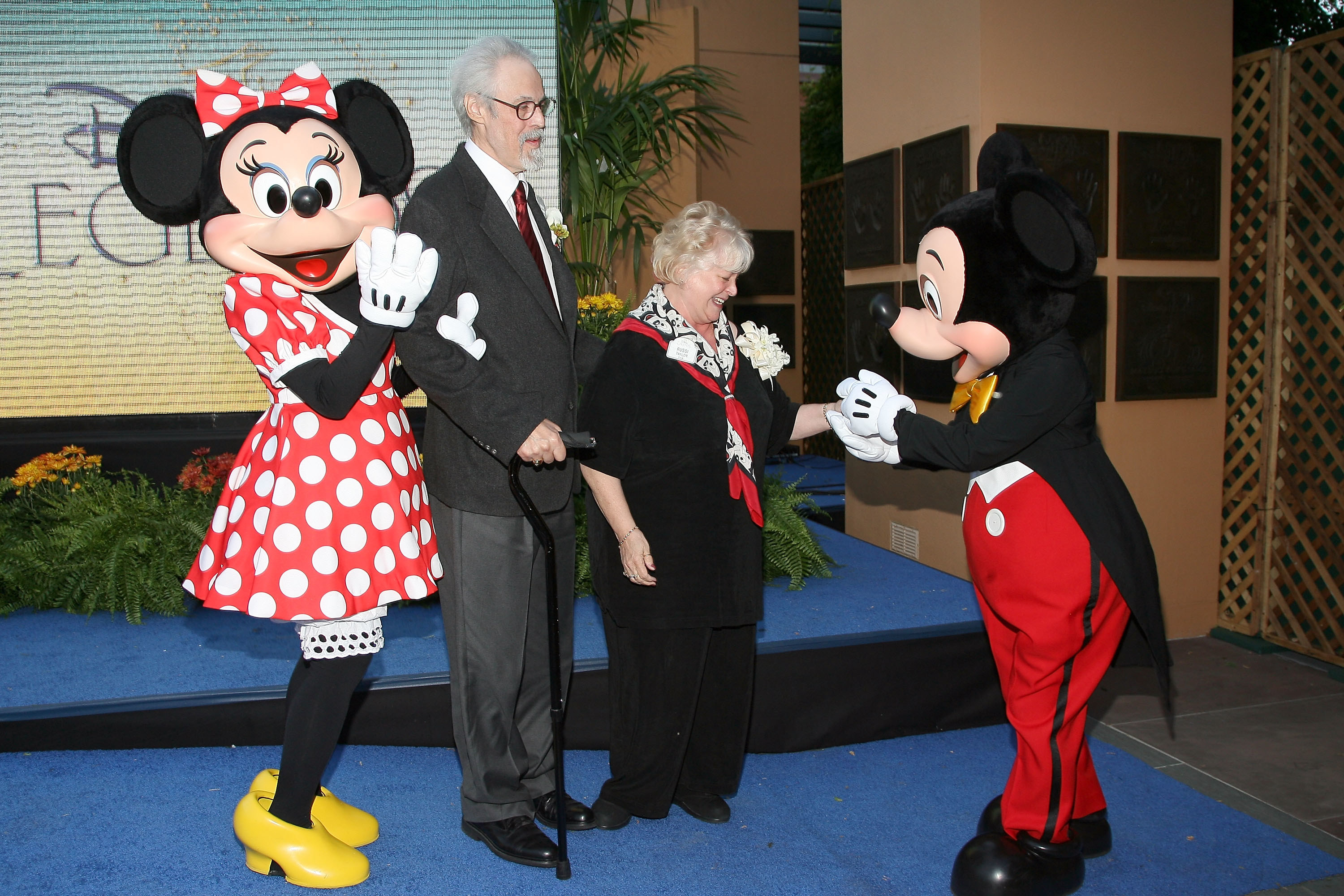 Wayne Allwine and Russi Taylor standing next to Minnie and Mickey Mouse, respectively, at a premiere.