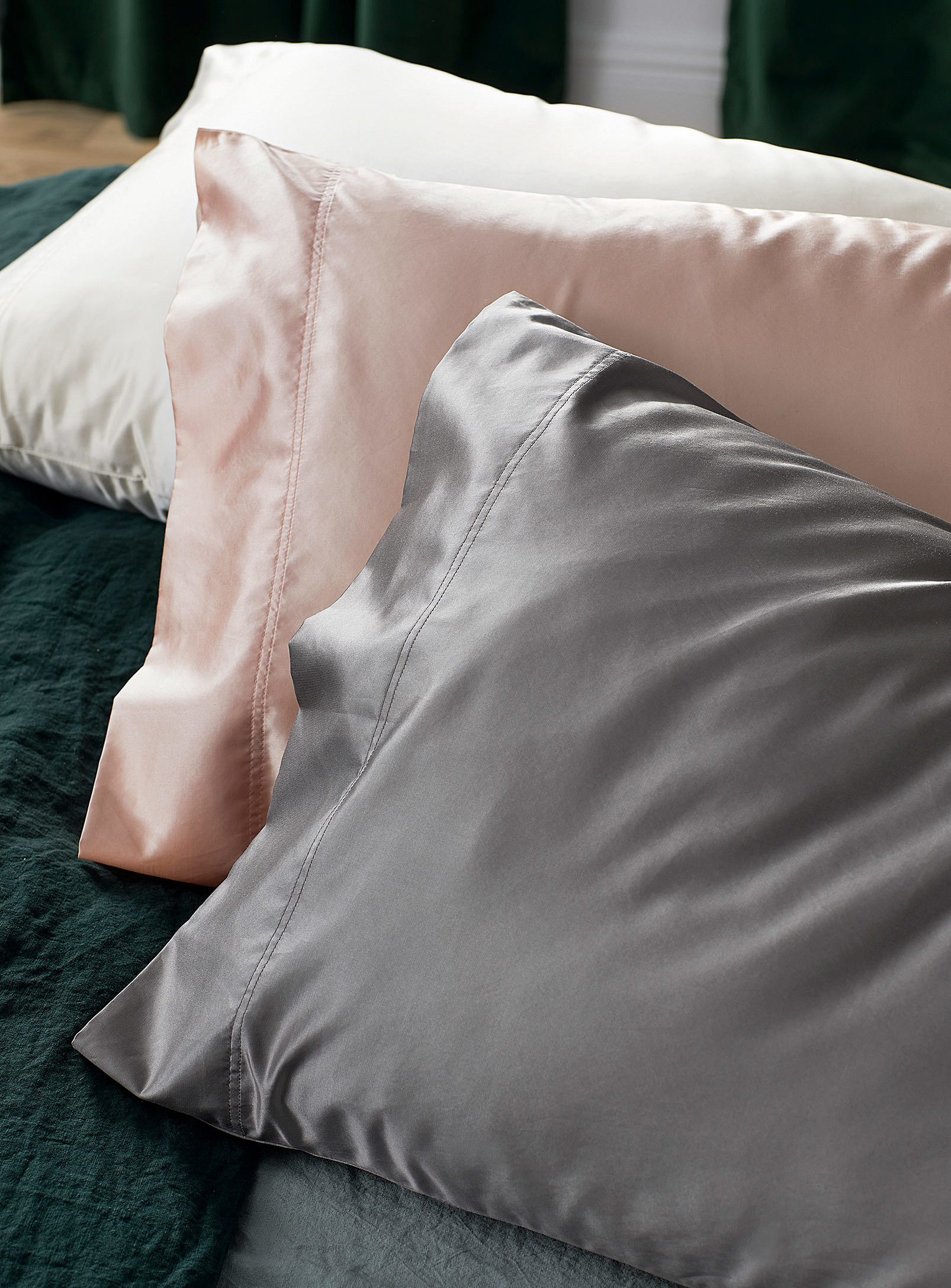 A trio of silky pillowcases on a bed