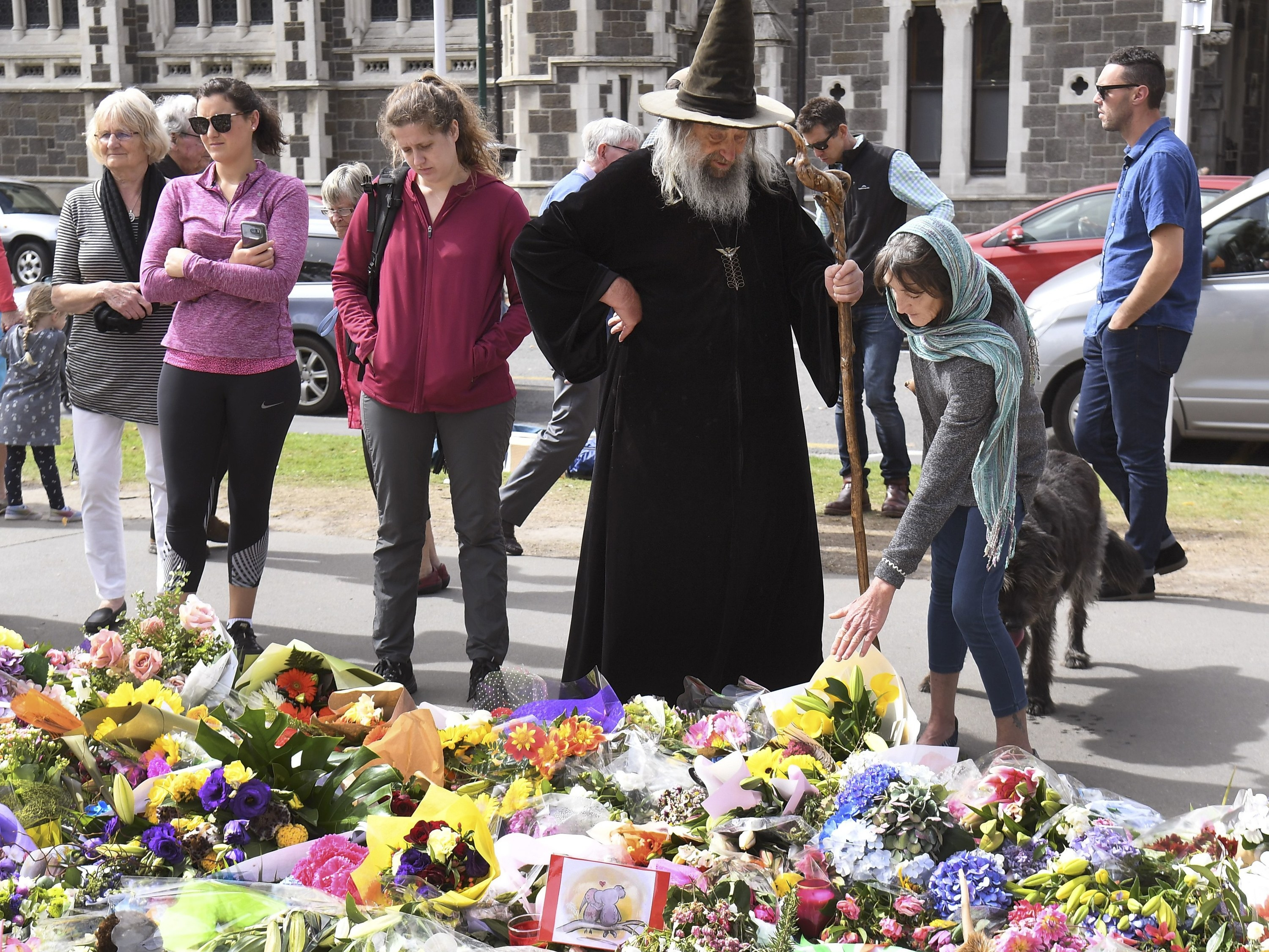 Wizard wearing dark robes standing in front of a memorial blanketed with flowers. There are many people surrounding him