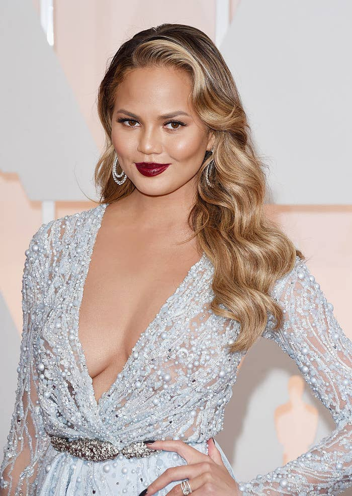 Chrissy posing on a red carpet in a beaded low-cut gown