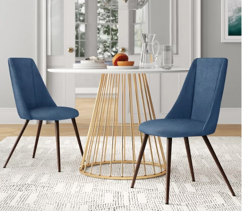 Two blue dining chairs around dining table