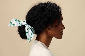 a model with a bow scrunchie around a low bun with a white and blue hydrangea print on it