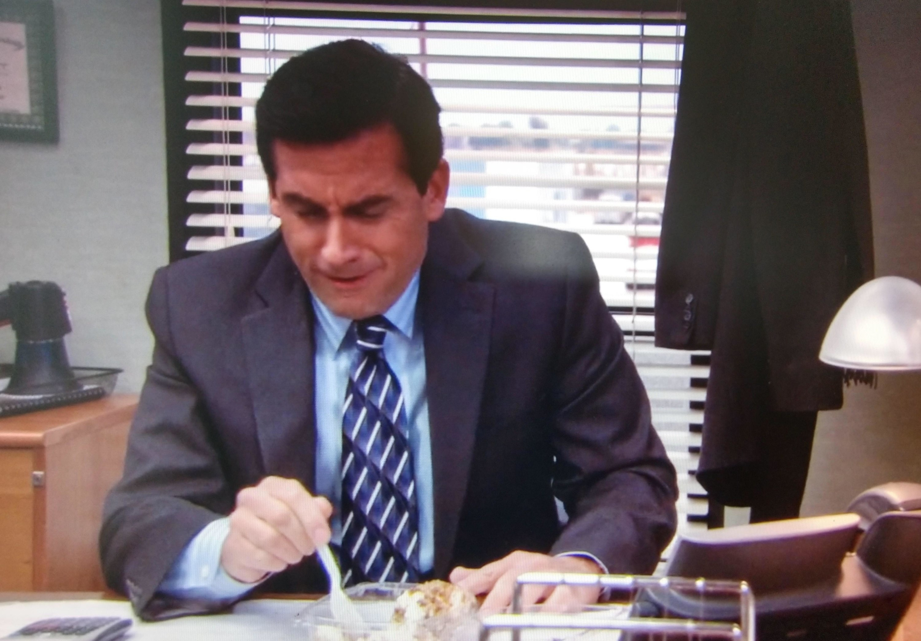 Michael eating some dessert at his desk while talking