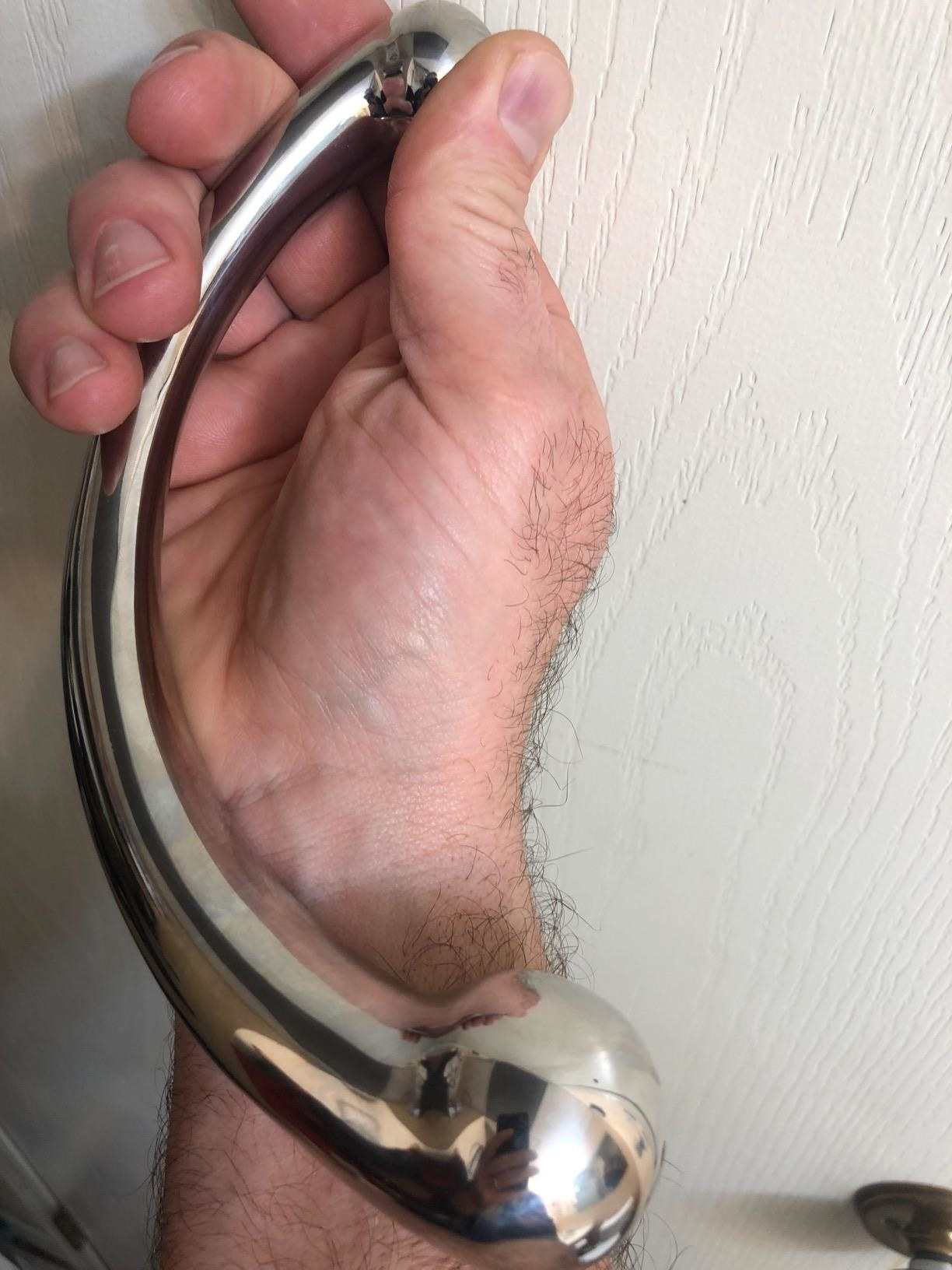 hand holding the curved wand with a large bulb on one end and a small bulb on the other