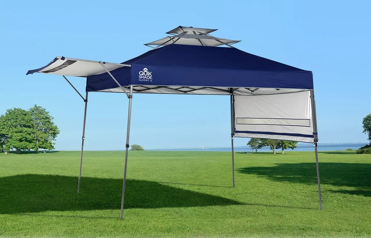 a navy pop up canopy in a field of grass
