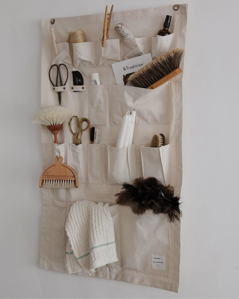 a canvas wall organizer mounted on a wall with cleaning and crafting supplies in each pocket