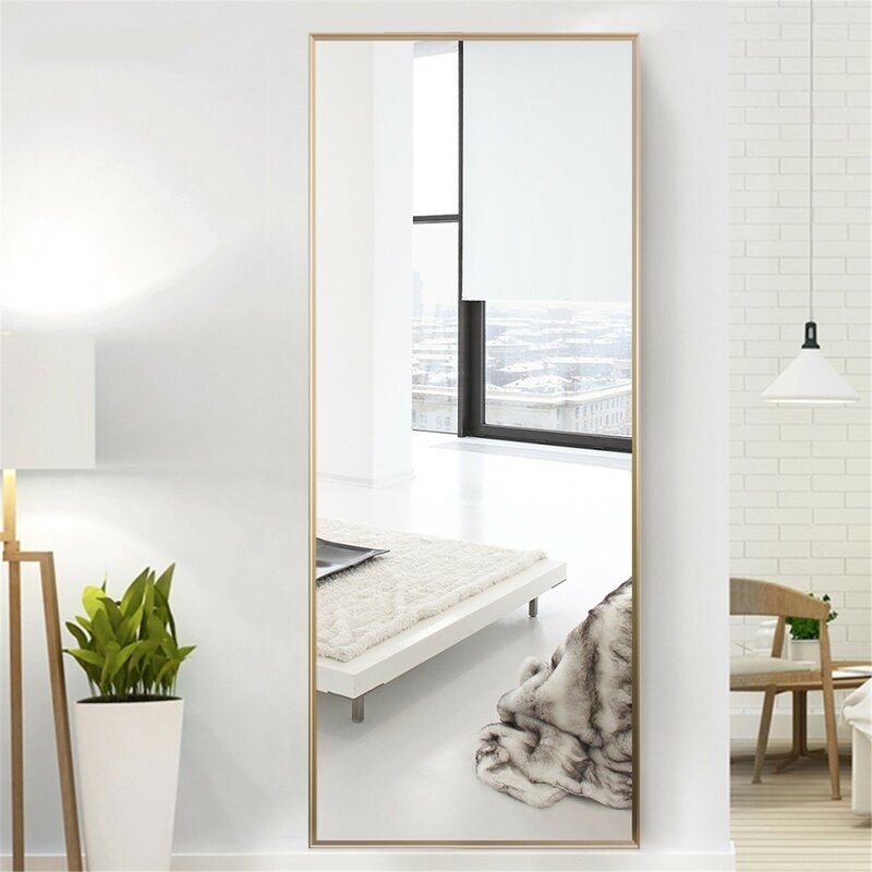 large rectangular mirror with gold trim mounted on a wall