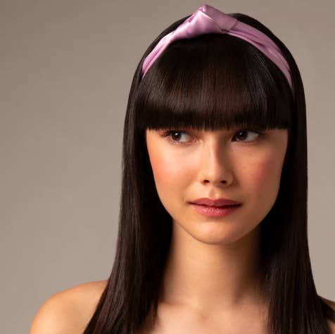 A person wearing the knotted silk headband while looking off camera